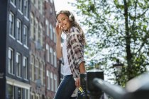 Netherlands, Amsterdam, smiling young woman with headphones and beer bottle on bridge — Stock Photo