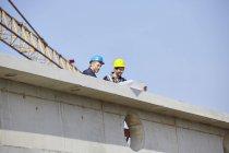 Двое мужчин на стройке рассматривают план строительства — стоковое фото