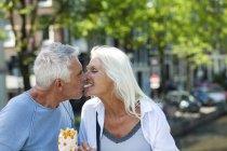 Netherlands, Amsterdam, happy senior couple sharing French Fries — Stock Photo