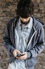 Молодой человек использует свой смартфон — стоковое фото