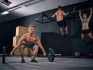 Drei Crossfit Athleten training im Fitness-Studio zusammen — Stockfoto