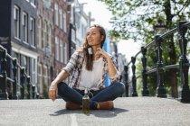 Нідерланди, Амстердам, молода жінка, що сидить з навушниками і пляшку пива на мосту — стокове фото