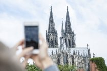 Germany, Cologne, young woman taking a picture of Cologne Cathedral with smartphone — Stock Photo