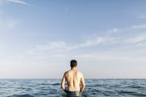 Back view of young man standing in the sea looking at distance — Stock Photo