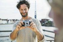 Smiling man taking picture at waterside — Stock Photo
