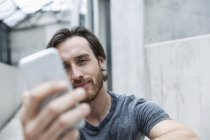 Portrait of young man looking at his smartphone — Stock Photo