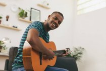 Man playing guitar at home — Stock Photo