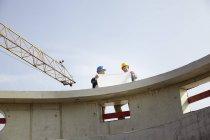Двое мужчин на стройке обсуждают план строительства — стоковое фото