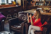 Blond woman sitting in a coffee shop taking pictures with her digital camera — Stock Photo