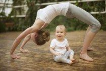 Женщина делает йога упражнений во время ребенка, наблюдая за ее — стоковое фото