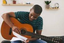 Hombre con guitarra de la escritura en papel - foto de stock