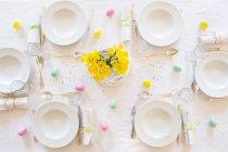 Puesto mesa de Pascua decorado con ramo de narcisos - foto de stock