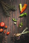 Peppers, chili peppers, tomatoes, onion and savory on wood — Stock Photo