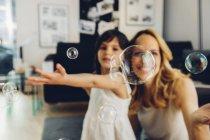 Mère heureuse avec sa fille à la maison soufflant des bulles de savon — Photo de stock