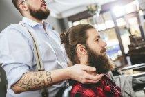 Mann mit Vollbart sitzen mit Friseur in barbershop — Stockfoto