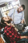 Barber with customer using digital tablet in barbershop — Stock Photo