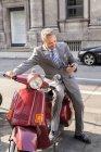 Lächelnde Geschäftsmann sitzt auf Motorroller — Stockfoto