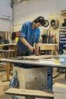 Carpenter using grinding machine — Stock Photo