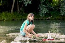 Дівчинка, граючи з дерев'яна іграшка човен в річці — стокове фото