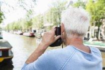 Homem sênior de Holanda, Amsterdam, tirar uma foto com uma câmera analógica em canal cidade — Fotografia de Stock