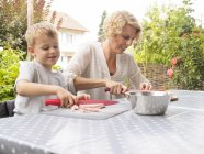 Madre e hijo preparando comida en la terraza - foto de stock