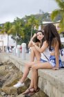 Mexico, Puerto Vallarta, two young women sitting at the Malecon in downtown — Stock Photo