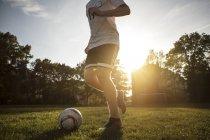 Низкий угол обзора подростка мальчика, играть в футбол на площадке — стоковое фото