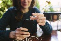 Jeune femme sur la musique écoute balcon avec téléphone intelligent — Photo de stock