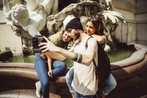 Austria, Vienna, group of three friends taking a selfie in front of fountain at Hofburg Palace — Stock Photo