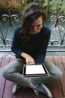 Giovane donna seduta sul balcone, che lavora con tablet digitale — Foto stock