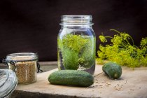 Closeup view of preserving jar of cucumbers over wooden background — Stock Photo