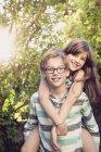 Хлопчик, даючи свою сестру скарбничку назад в саду — стокове фото