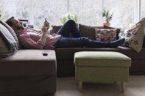 Uomo maturo sdraiato sul divano a controllare i messaggi su smart phone — Foto stock