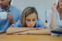 Frustrated girl sitting with distracted parents at table — Stock Photo