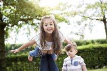 Портрет маленькой девочки, балансирующей на ногах матери, мальчик на заднем плане — стоковое фото