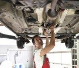 Mécanicien automobile travaillant dans le garage de réparation, vérification sous la carrosserie d'une voiture — Photo de stock