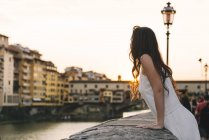 Italy, Florence, woman watching sunset behind Ponte Vecchio — Stock Photo