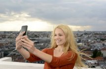 Germany, Berlin, young woman taking a selfie with her smartphone — Stock Photo