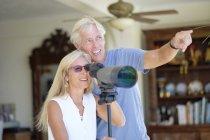 Senior couple looking through telescope — Stock Photo