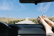Spanien, Menorca, Füße auf dem Armaturenbrett, in den Ferien mit einem Leuchtturm im Hintergrund leer Straßenfahrt — Stockfoto