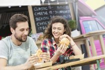 Young couple eating sandwiches in outdoor gastronomy — Stock Photo