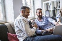 Two smiling businessmen sharing laptop — Stock Photo