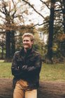Retrato de jovem sorridente com braços cruzados no parque outonal — Fotografia de Stock