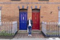 Молодой человек стоит перед кирпичным домом — стоковое фото