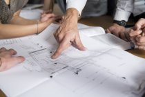 Cropped image of hand pointing on construction plan — Stock Photo