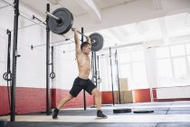 Physical athlete weightlifting with barbell in gym — Stock Photo