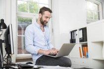 Lächelnder junge Mann im Büro sitzen am Schreibtisch mit laptop — Stockfoto