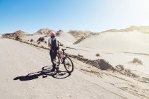 Чили, женщина толкает горный велосипед через долину Луны в пустыне Атакама — стоковое фото