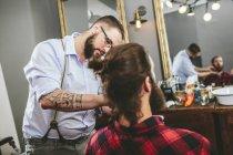Peluquería cepillo barba de un cliente en peluquería - foto de stock