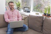 Зріла людина сидить на дивані, використовуючи ноутбук — стокове фото